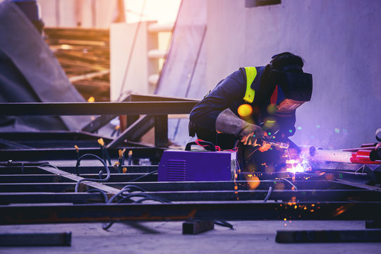 Worker welding steel with sparks at outdoors construction site