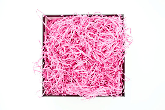 Shredded pink paper packing material in a square box. Pink spaghetti shredded packing paper used to protect fragile object while in transport. The box is isolated on white background with copy space.