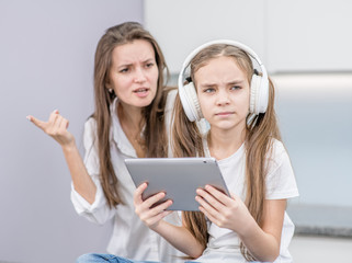 Mother scolds her teenage daughter, girl is listening to music in headphones and ignoring her mom. Family relationships