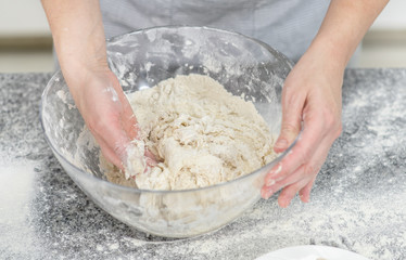 Female hands making dough in the kitchen at home. Top view
