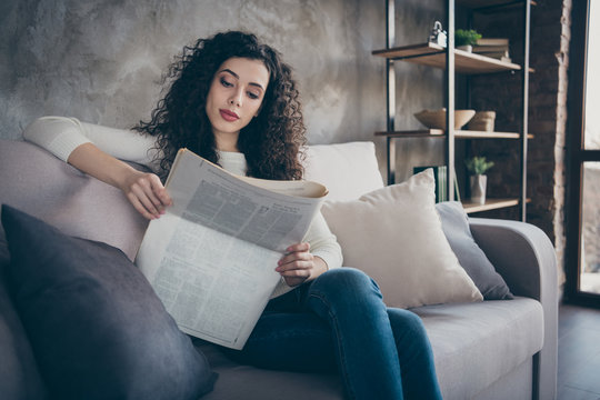 Portrait of her she nice attractive charming lovely cute focused peaceful wavy-haired girl sitting on divan reading digest news at modern industrial loft interior style room indoors