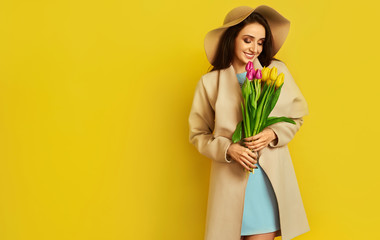 Beautiful girl  dressed in a beautiful coat and hat, with flowers tulips in hands over yellow background. Young woman received flowers as gift and rejoices. Spring girl with flowers. March 8.