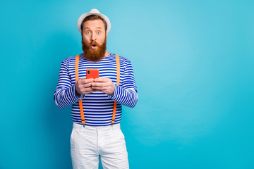 Astonished man rest relax use cellphone read social network information impressed look scream wow omg wear white shorts panama orange suspenders sun isolated over blue color background
