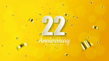 22nd anniversary background with illustrations of white numbers and pieces of gold paper on a soft yellow background.