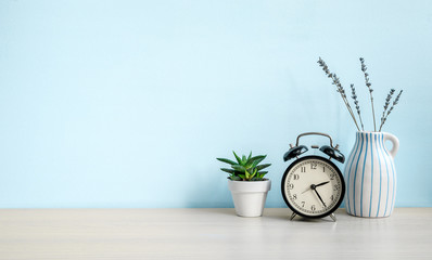 Empty blue wall and desk with alarm clock, home plant and ceramic vase. Copy space Fotomurales