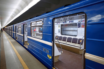 Minsk, Belarus. Jan 2020. Blue train standing with an open sliding mechanical door at a train station platform. Last stop. Wagons of subway in underground. Rapid transport. High-speed electric train.