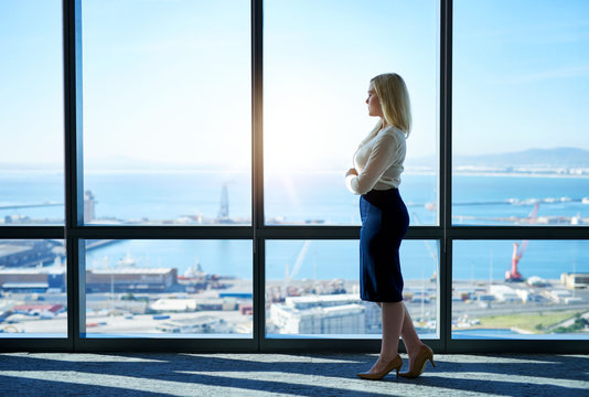 Young businesswoman looking at the city through office building windows