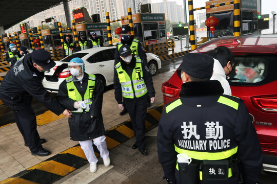 Police officers wearing masks check the boot of a car for smuggled wild animals following the outbreak of a new coronavirus, at an expressway toll station on the eve of the Chinese Lunar New Year celebrations, in Xianning