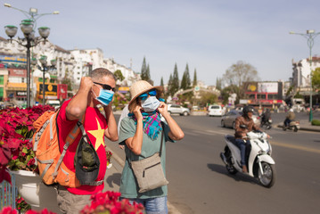 Woman and man wearing sanitary mask outdoors in Da Lat city centre Vietnam. Medical mask protection against risk of chinese flu virus epidemy in Asia. Anti smog mask traffic pollution.
