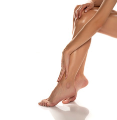 woman applying lotion on her legs