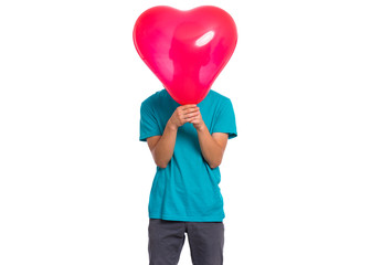 Fototapete - Teen boy hiding behind red heart shaped balloon. Child holding symbol of love, family, hope. Celebration of Saint Valentines Day. Teenager cover face isolated on white background.