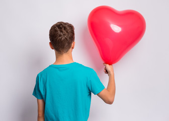 Fototapete - Back view. Portrait of teen boy holds red heart shaped balloon, on grey background. Child in blue t-shirt holding symbol of love, family, hope - rear view. Valentines Day concept.