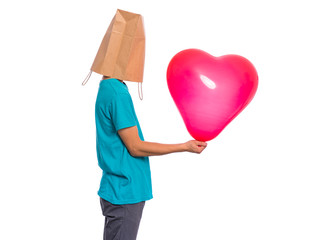 Fototapete - Valentines Day concept. Teen boy with paper bag over his head holds heart shaped balloon, isolated on white background. Boy holding symbol of love, family, hope. Teenager cover head with bag.