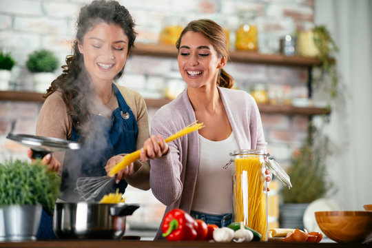 Two friends having fun in kitchen. Sisters cooking together.