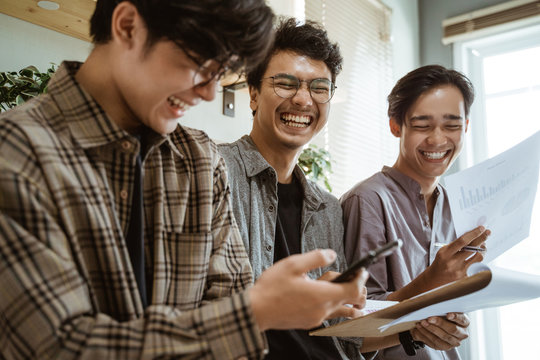 three young asian worker chatting about their product at work