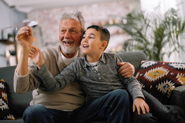 Grandfather teaching his grandson how to make paper airplane. Grandpa and grandchild playing together.