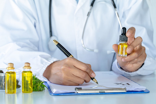 Doctor holding a bottle of hemp oil and offer to patient medical marijuana and oil.  alternative remedy or medication,medicine concept.