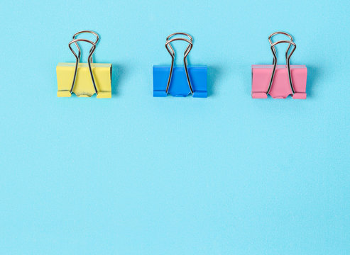 Colorful binder clips on blue paper background.