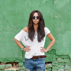 Outdoor street fashion portrait of stylish beautiful woman posing in blue jeans and sunglasses