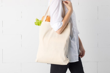 Girl is holding cotton eco-bag with green fresh kale and bread.