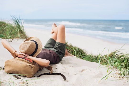 Young woman resting by the sea. Girl lying down on the beach. Enjoying life, summer lifestyle, relaxation and travel concept