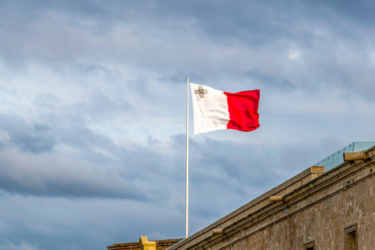 Malta flag on a flagpole waving on a bright sky with clouds background