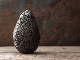 Whole ripe brown hass avocado fruit on dark table. Healthy fats. Side view, copy space