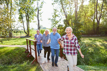 Fototapeta Senioren laufen fröhlich auf einem Wanderweg
