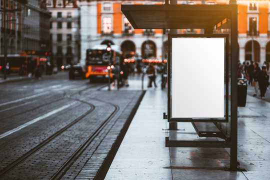 A blank advertising billboard placeholder template on the city street; an empty mock-up of an outdoor poster on a paved tram stop; a white vertical mockup of an urban banner on the bus stop