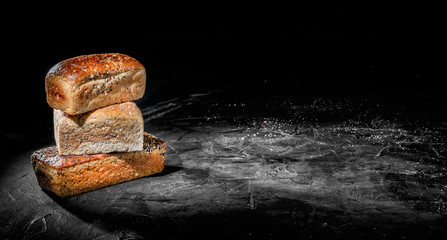 Assortment of baked bread and bread rolls on dark background