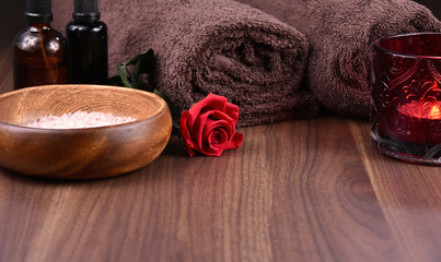 Romantic spa and wellness still life with red rose stock images. Spa and wellness setting. Red rose, bath salt, brown towels, cosmetic phials and candle on a wooden background with copy space for text