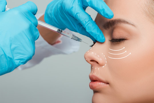 cropped view of cosmetologist making beauty injection in nose to attractive woman isolated on grey