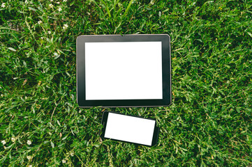 Mock up tablet and smartphone on green grass. The concept on the topic of technology and recreation.