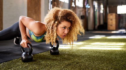 Focused woman working out with weights on a gym floor