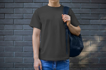 Mockup of a black men's t-shirt on a young guy against a brick wall, front view. Wall mural