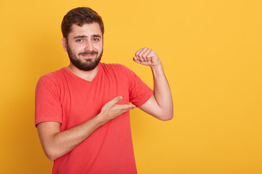 Horizontal shot of male wearing red casual t shirt show his weak biceps muscles, attractive young handsome unshaven man posing isolated over yellow wall background, needs some sport training.