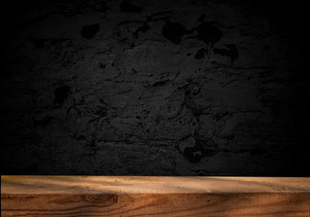 Empty wooden table on a background of dark blurred wall, empty space for product above.