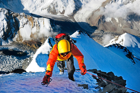 Climber ascending the summit of mountain peak. Climbing and mountaineering sport concept, Nepal Himalayas