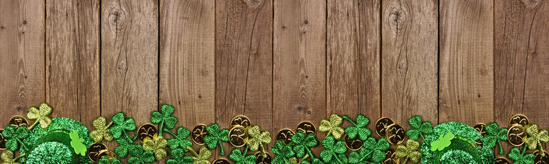 Wall Mural - St Patricks Day banner with border of shamrocks, gold coins and leprechaun hat. Above view over a rustic wood background. Copy space.