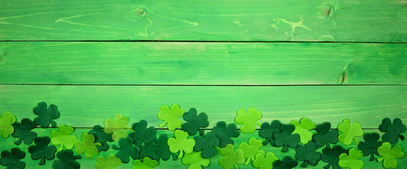 St Patricks Day banner with bottom border of shamrocks. Overhead view over a green wood background. Copy space. Wall mural
