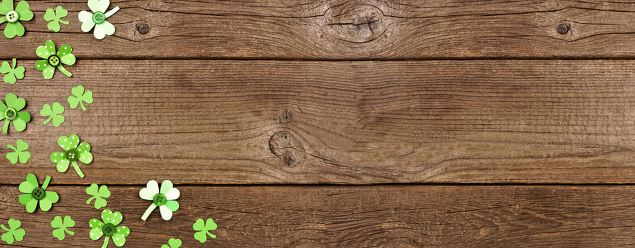St Patricks Day banner with corner border of handmade paper button shamrocks. Top view over a rustic wood background with copy space.