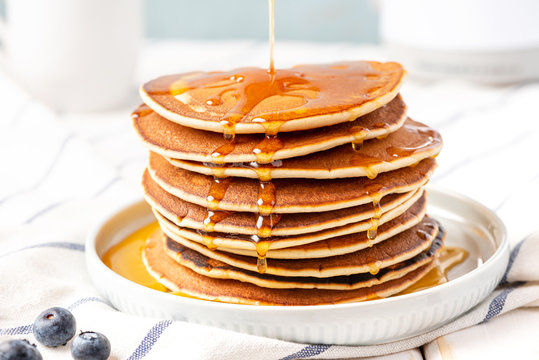Pancakes with maple syrup in a plate on the table. Sweet tasty breakfast, dessert.