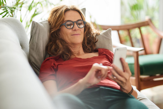 Smiling mature woman lying on her couch using a cellphone