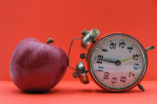 Red apple and inverted vintage alarm clock on neon red background. Concept time for yourself.