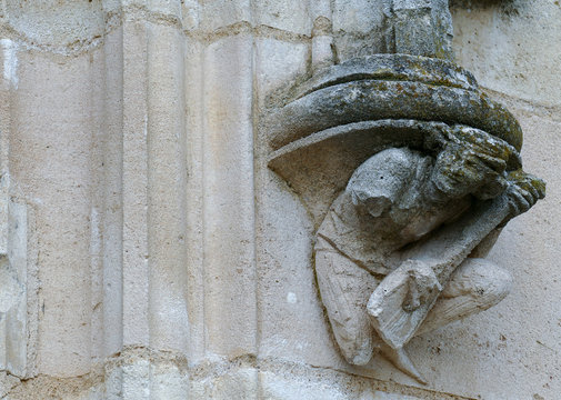Closeup architectural details of ancient historic castle or chateau in France - guitar lute player sculpture