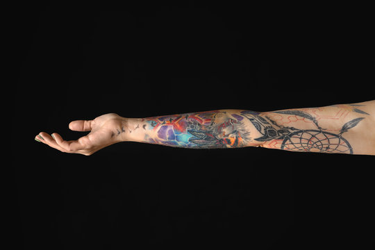 Woman with colorful tattoos on arm against black background, closeup