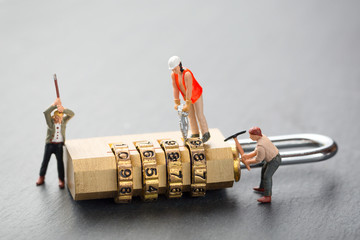 Concept of hacking attack and security problems. Miniature people try to unlock metal padlock