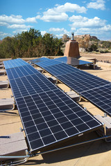 Solar panel installation on a flat New Mexico roof, in vertical format