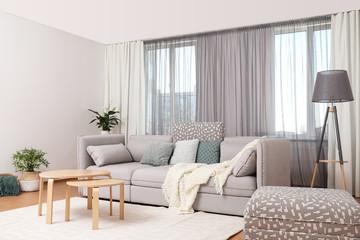 Windows with stylish curtains in living room interior