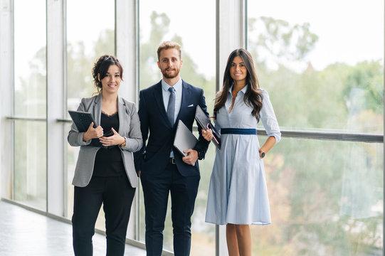 Portrait of confident business team holding portable devices